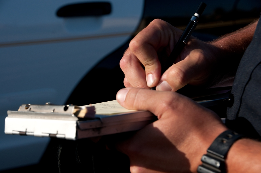 a close up of a police officer's hands as he writes a traffic ticket.